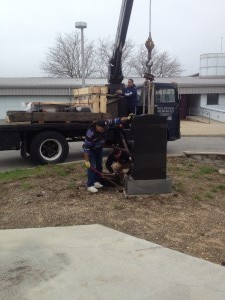 Workers from Wellwood Memorials prepare the centerpiece for transfer